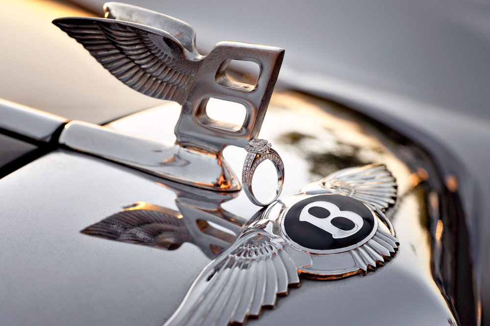Bride's engagement ring on hood ornament of Bentley in Redlands.