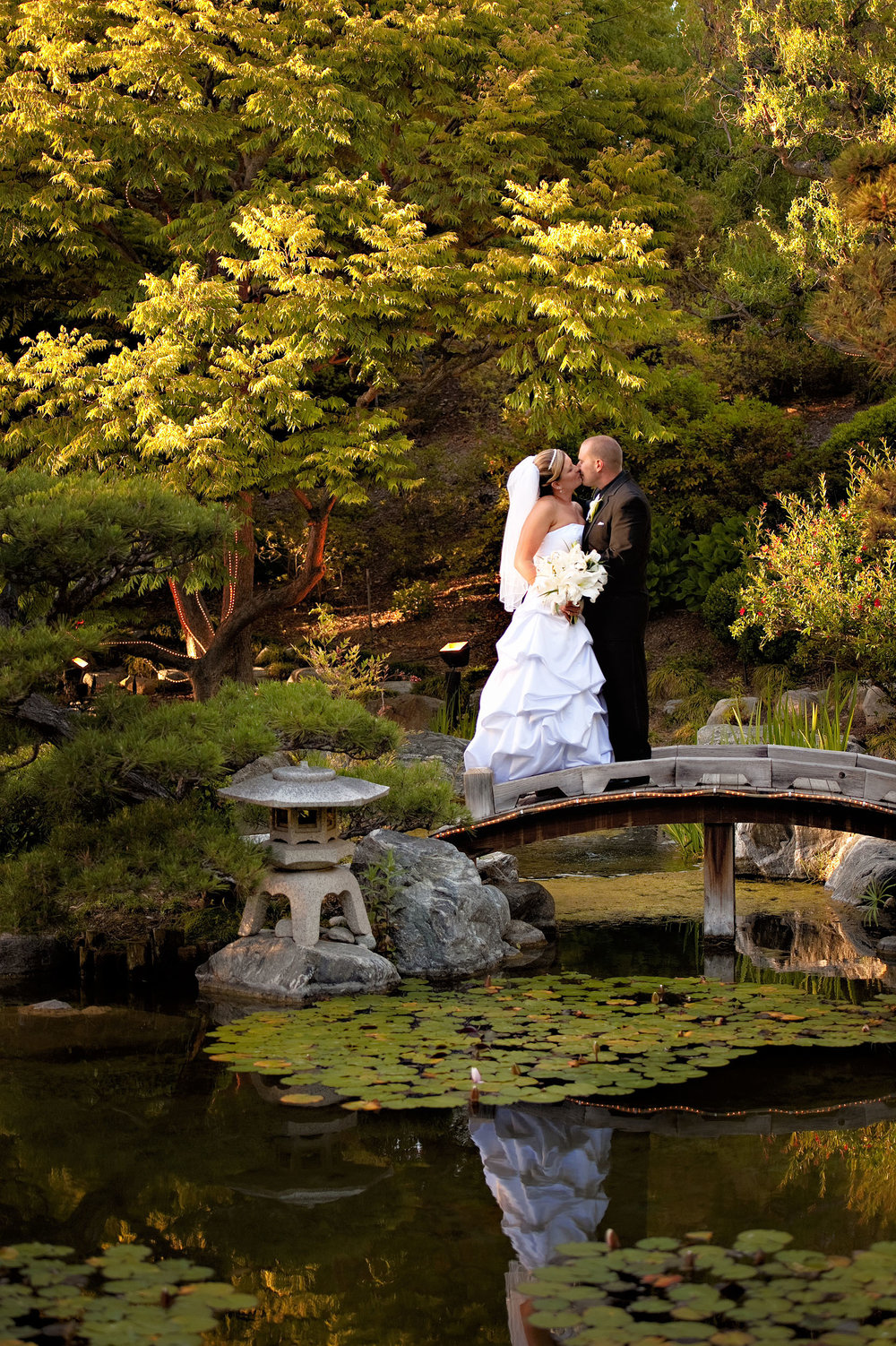Bride and groom kissing  on bridge in Japanese Garden at the Sorrento Mesa Karl Strauss Brewing Company in San Diego.