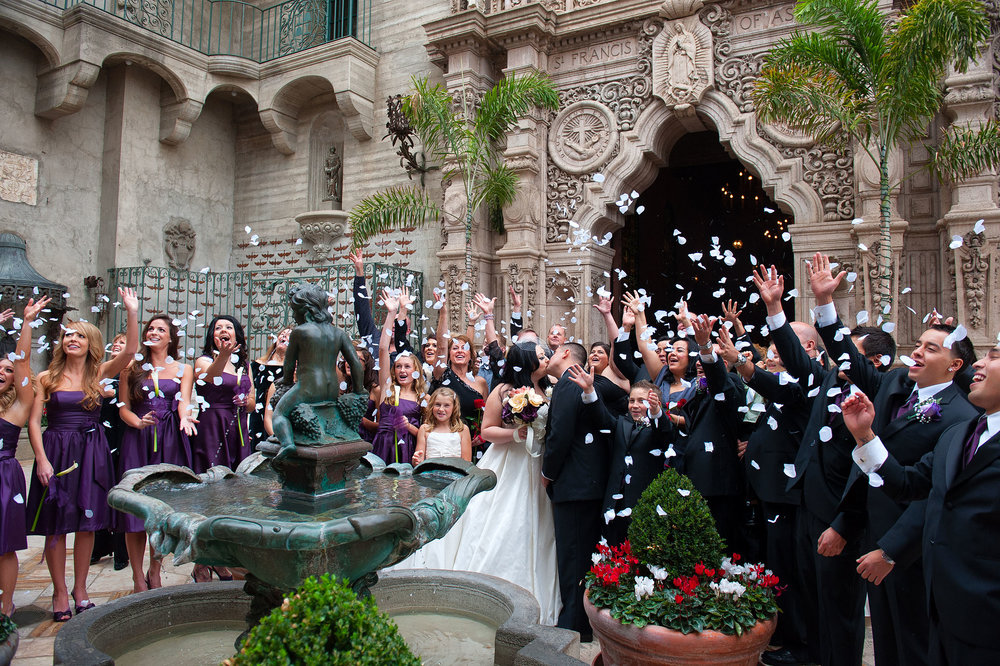 Bride and groom kissing by fountain with guests throwing rose petals at the wedding cathedral at the Mission Inn Hotel & Spa in Riverside.