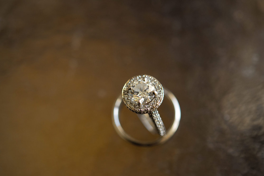 Bride's engagement diamond ring solitaire balanced in groom's wedding ring.