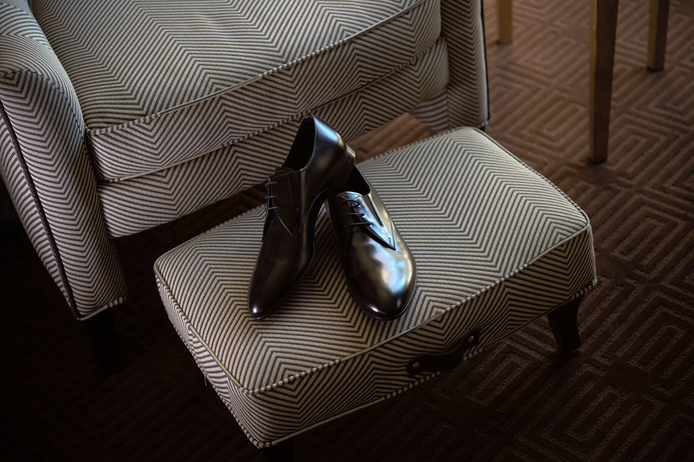 Groom's shoes on ottoman in front of chair.