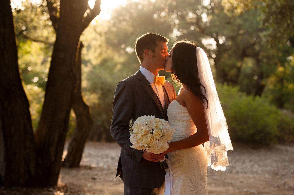 Bride and groom kissing amongst the trees at sunset.