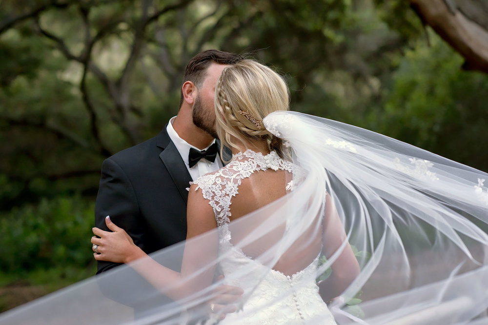 Bride and groom with flowing veil at Temecula Creek Inn in Temecula.