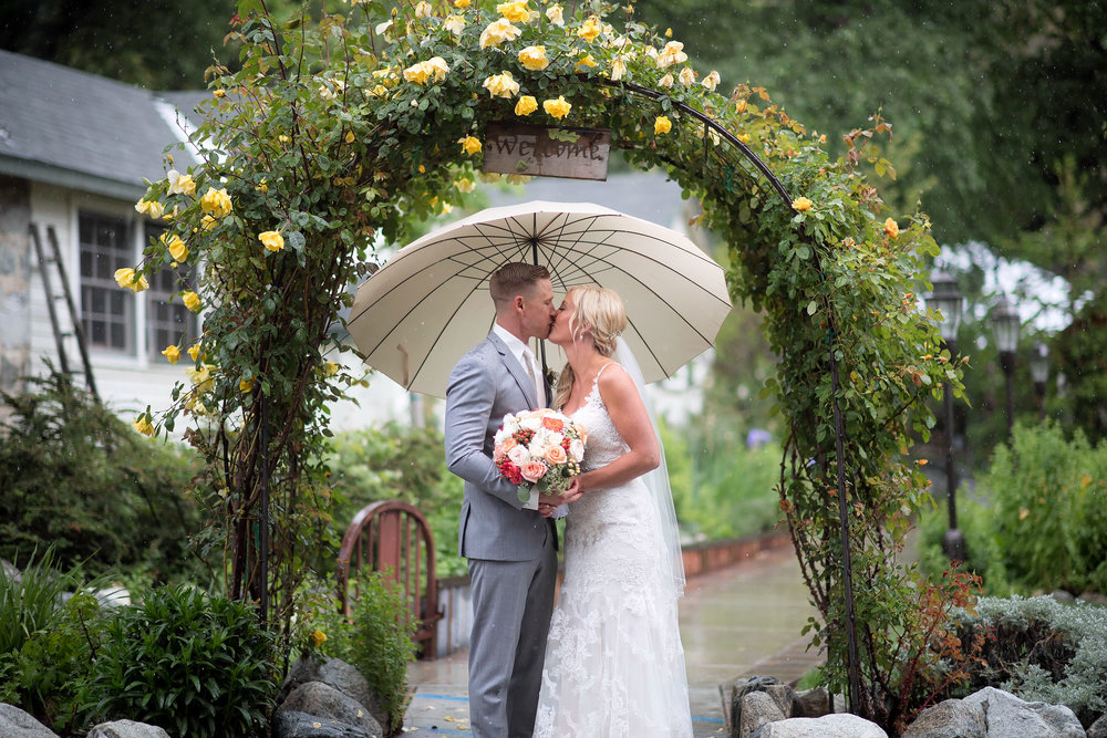 Bride and groom under umbrella and arch at The Homestead in Oak Glen.
