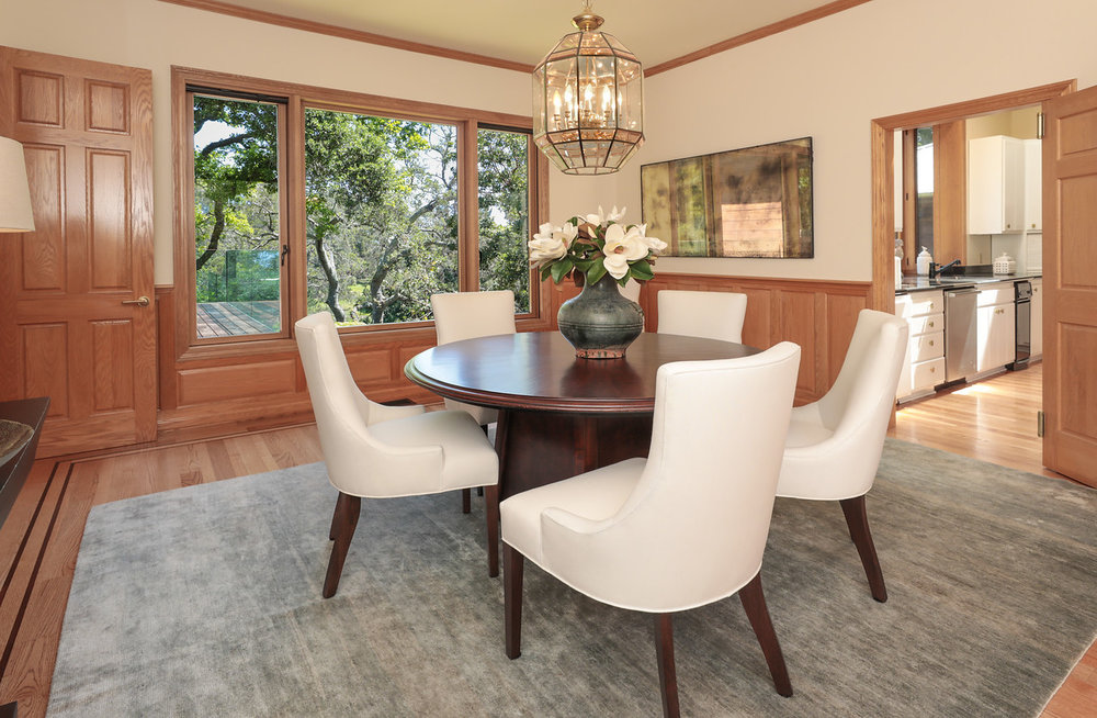 DINING ROOM  Formal paneled wainscot, glass chandelier, and wide window showcasing golf course views