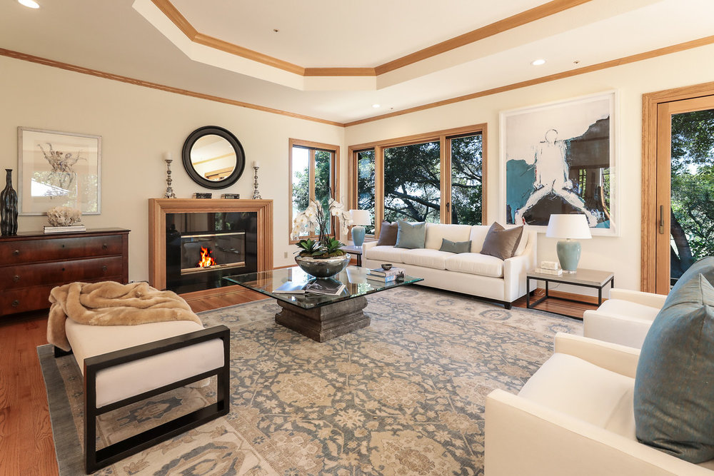 LIVING ROOM  Steps ascend to the living room outlined with expansive windows and sliding glass doors to the wraparound deck and views; tray ceiling with recessed lights and wood-burning fireplace surrounded in granite