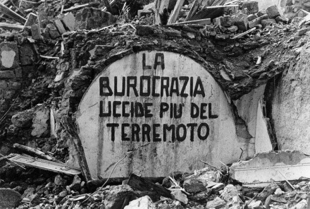 """Slogan dipinto su un muro distrutto di Salaparuta, """"La burocrazia uccide più del terremoto"""", 1968"""