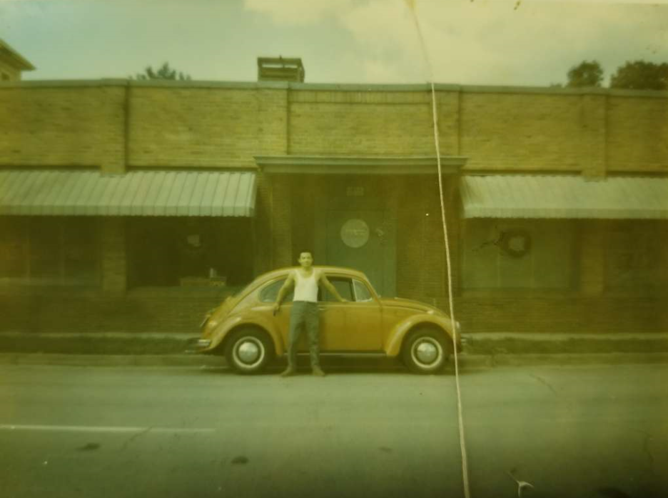 Kim Soo in 1968 leaning on his first vehicle with his green card in his hand outside the Downtown Houston building that would become his dojang.