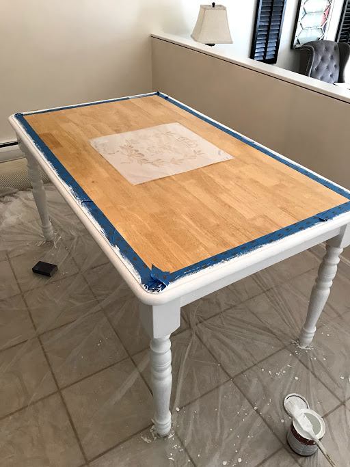 And here is my Modern Farmhouse style table painting project underway. First I sanded it down (see sander on the floor there). Then I just painted the legs and surround on the top. Below is a plastic drop cloth from the hardware store for $7. I will tell you: that's always $7 WELL SPENT since I'm not the most careful painter.