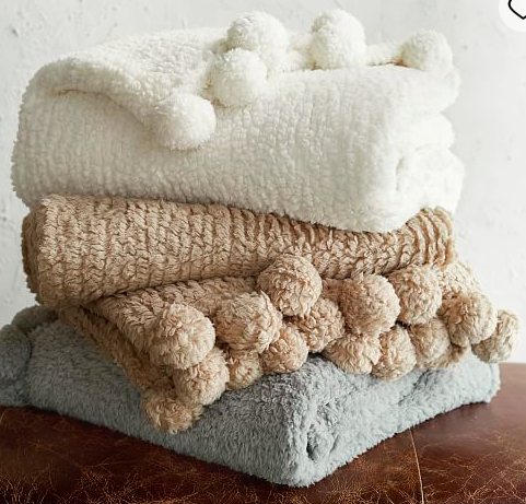 Cozy Pom Pom Throws - I think everyone needs a cozy throw for snuggling up on their couch under. Give me fleece. Give me pom poms. These are perfection.