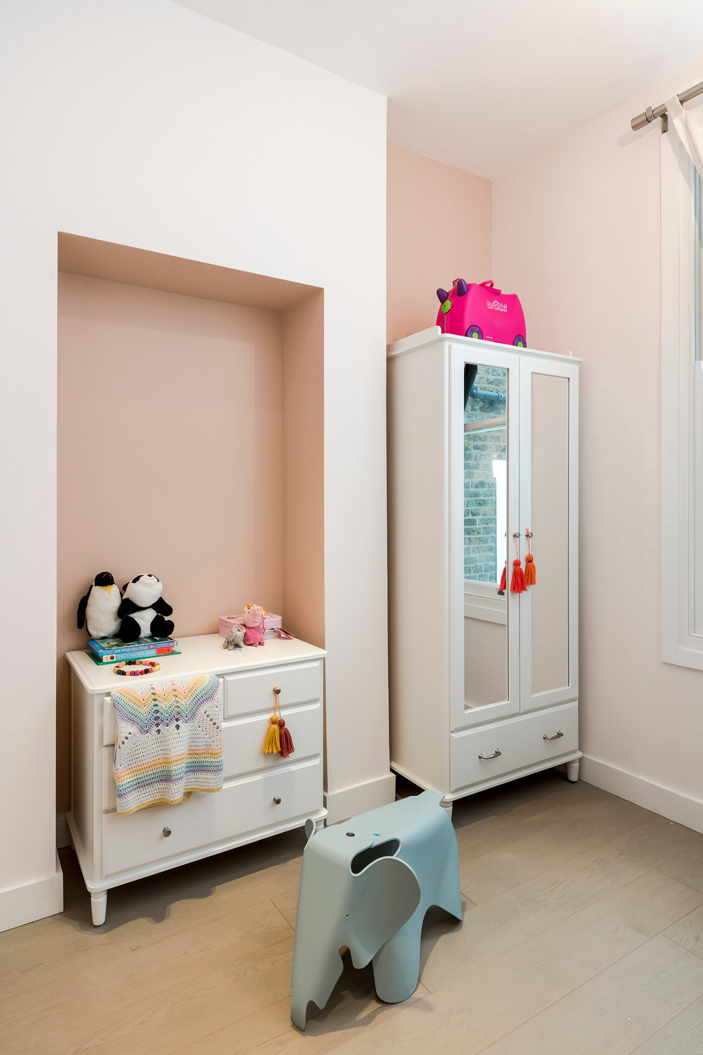 Daughter's bedroom with hues of pink, layout was kept to house the client's existing furniture.