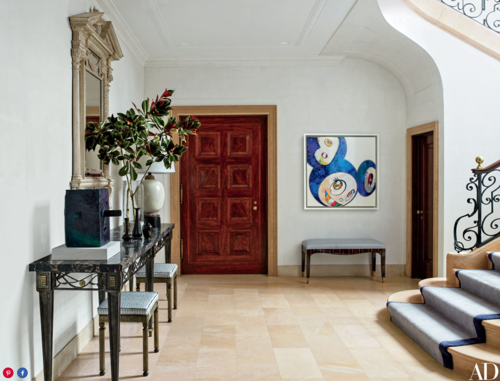 In the entrance hall, a late-19th-century mirror from O'Sullivan Antiques is mounted above a circa-1920 Art Deco console from Florian Papp and a pair of vintage Axel Einar Hjorth stools from H. M. Luther; beneath the Takashi Murakami painting is a '30s Art Deco bench from Karl Kemp Antiques.