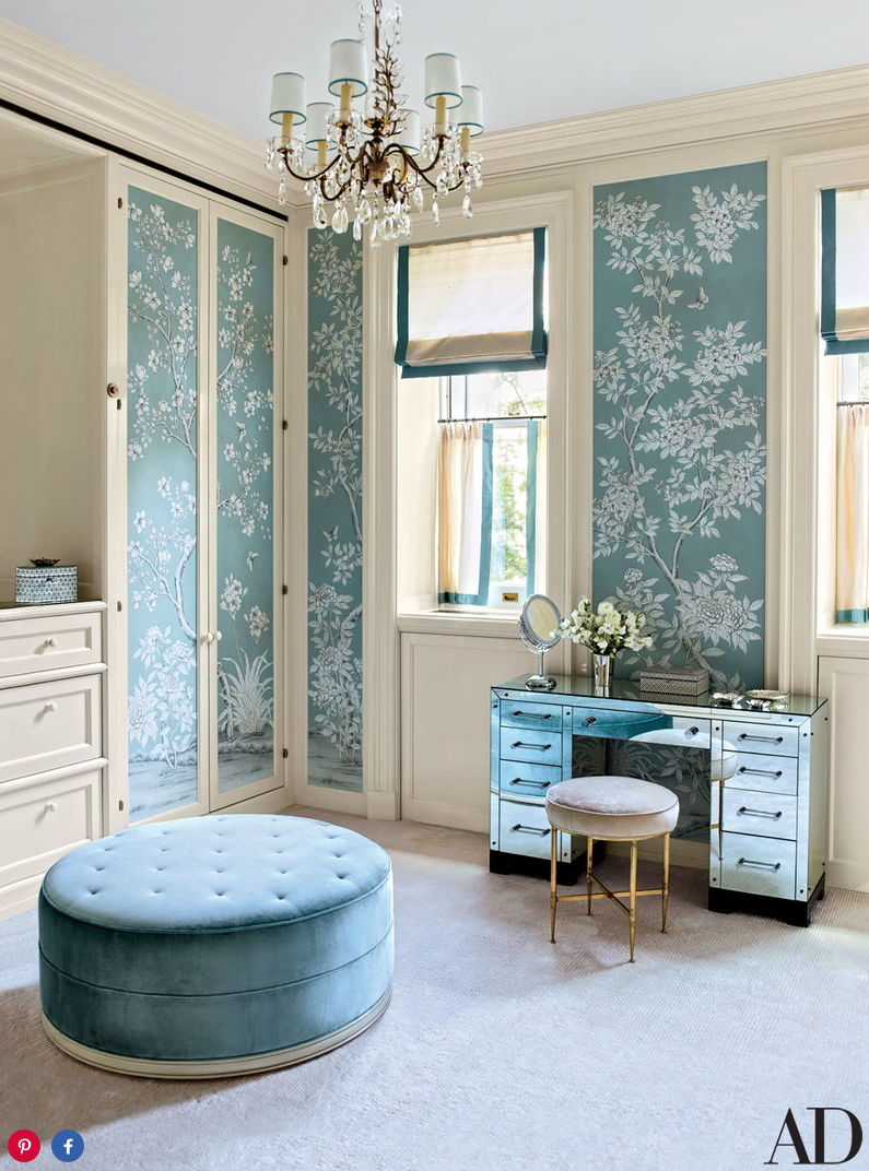 The wife's dressing room, lined in a hand-painted Gracie wallpaper, is furnished with an American mirrored desk and an Italian brass stool, both vintage pieces from John Salibello, as well as an S. R. Gambrel–devised ottoman covered in a Clarence House silk