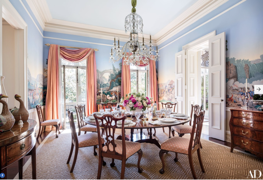 An antique Zuber wallpaper depicting Revolutionary War scenes lines the dining room; the 19th-century Waterford chandelier is from Nesle, and the dining table is English.