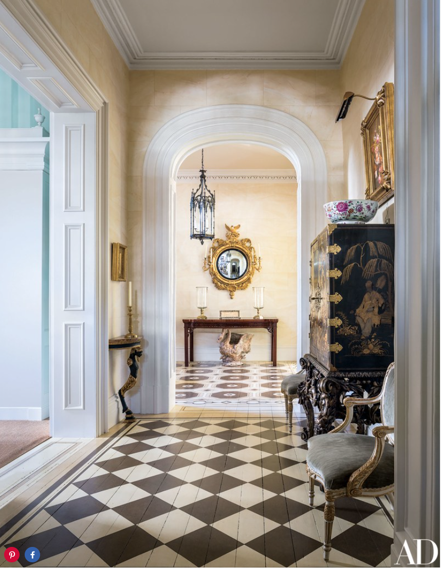 As seen from the entrance hall, a Regency mirror from Mallett is mounted in the stair hall, above an 18th-century table from Florian Papp.
