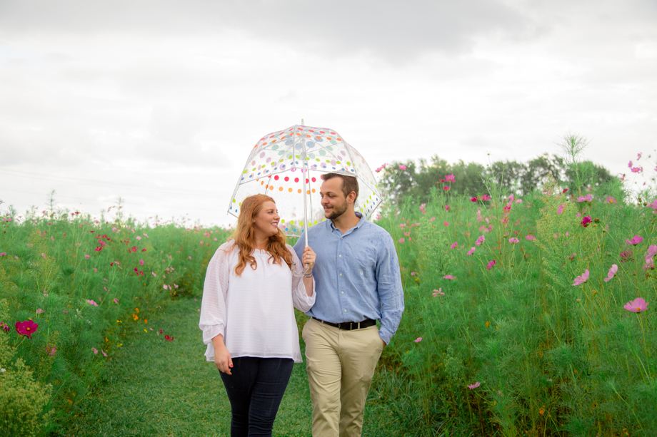 These two - braved the rain and walked through the wildflowers with an umbrella.