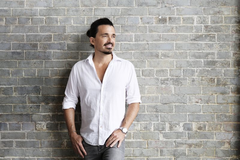 Sidney Torres leaning against stone wall