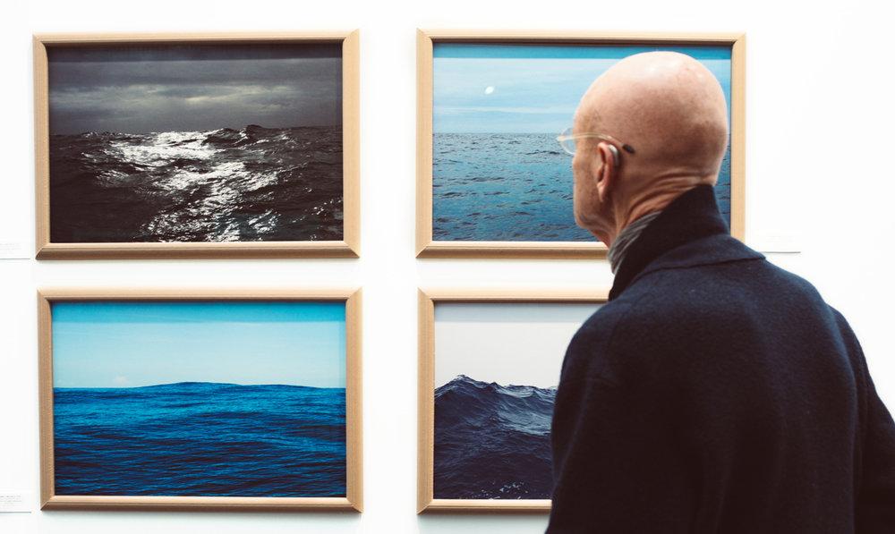 Man looking at gallery images of ocean