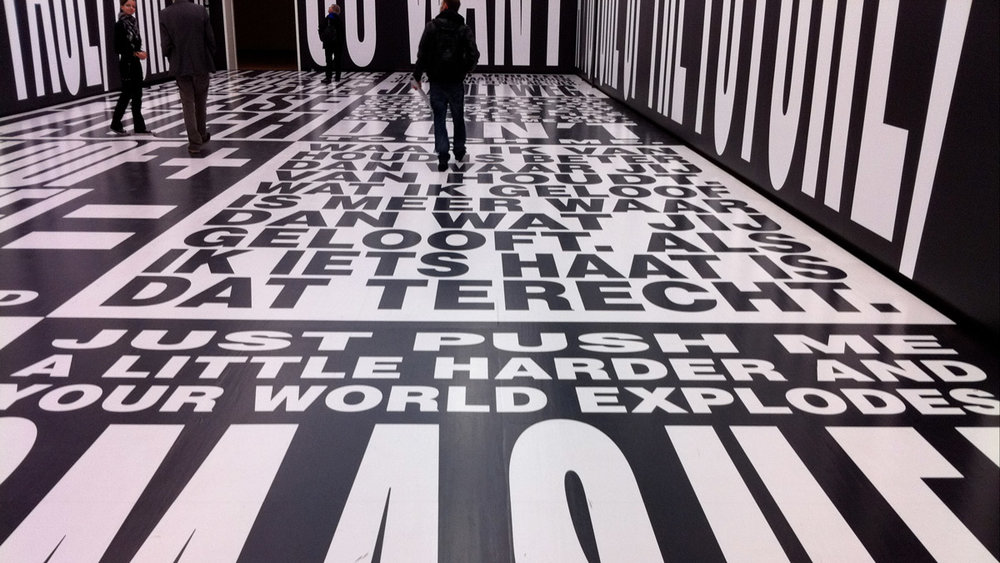 People in room with typography on floors and walls