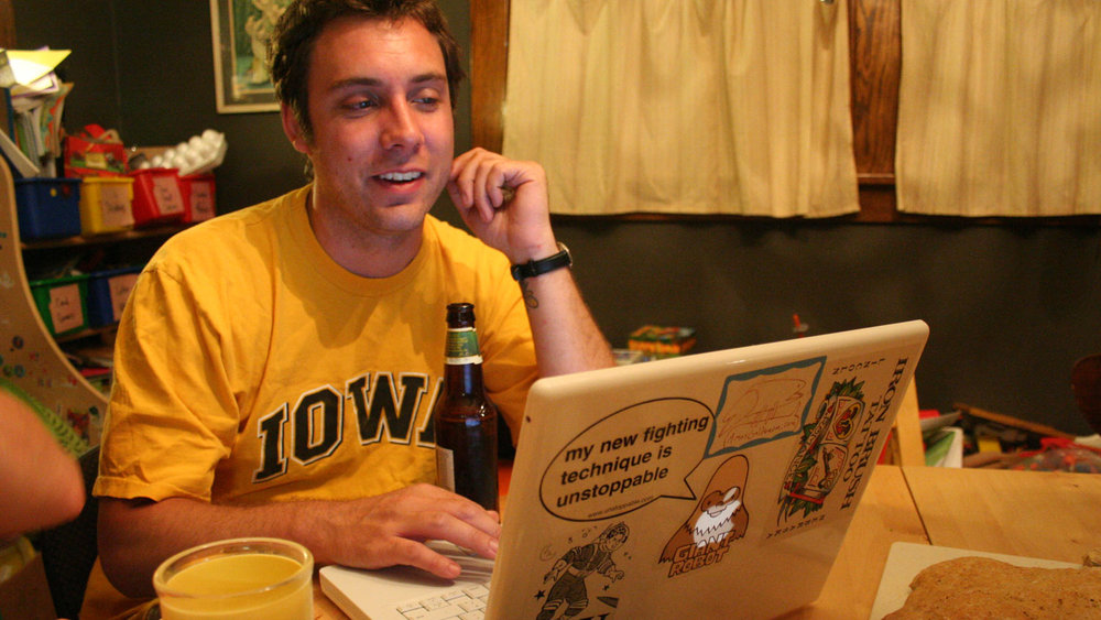 Man in yellow Iowa t-shirt smiling and using laptop while having a beer