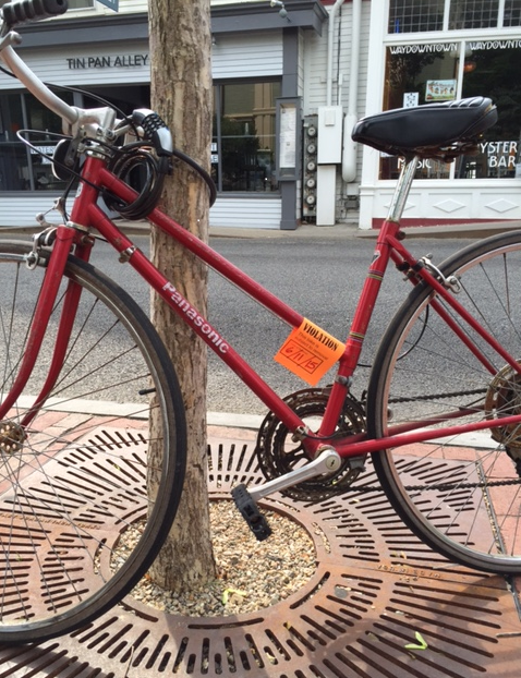 An orange ticket on a bicycle for locking a bike to a street tree in front of Town Hall in Provincetown
