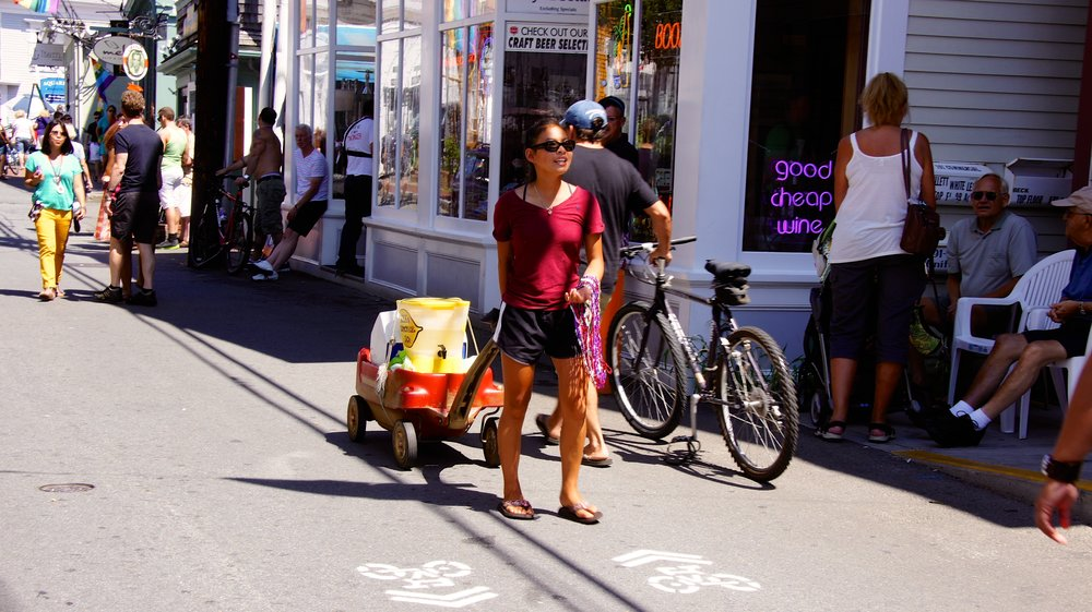 """The """"Lemonade Girl"""" with her wagon and the temporary sharrows on Provincetown's Commercial Street during summer 2012."""