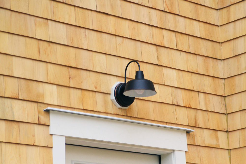 Oil rubbed bronze exterior farm lights with architrave trim surrounding doorways and windows… -