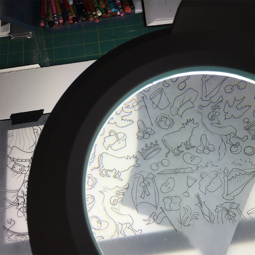 using my handy magnifying lamp, i put transfer paper between my patterned tracing paper and my watercolour paper so i can retrace all the icons so i know where to paint.