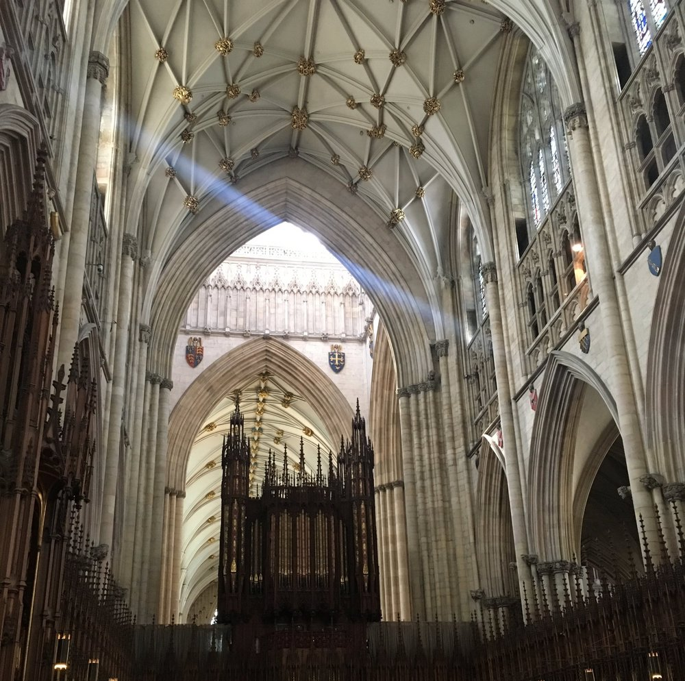 Interior of York Minster with more empty niches, and some with headless statues.