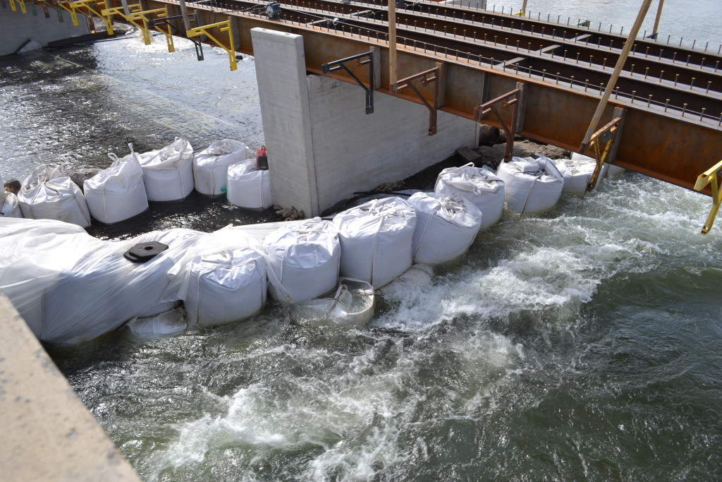 Large sandbags are used to form a cofferdam to divert water during construction.