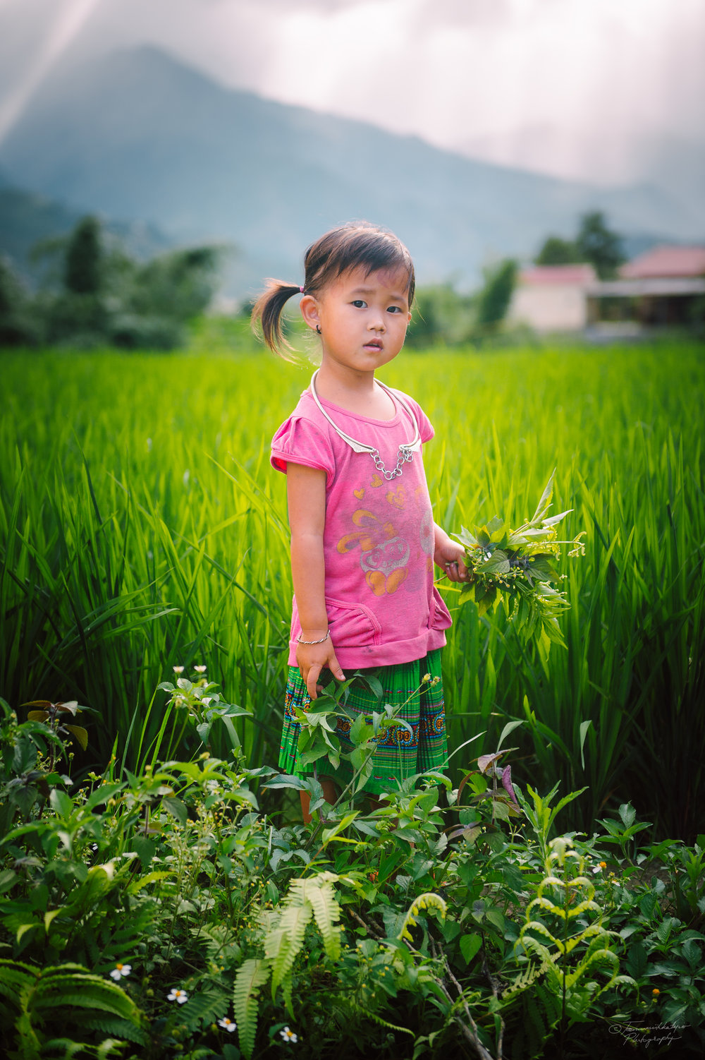 A girl picking flowers. The necklace is believed to bring good luck and keep the child safe.