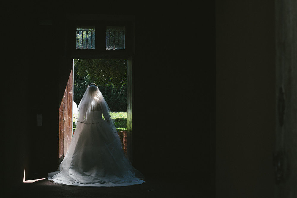 Moody portrait of a bride looking out the door in her wedding gown by Proovias Barcelona. Image by Oceânica
