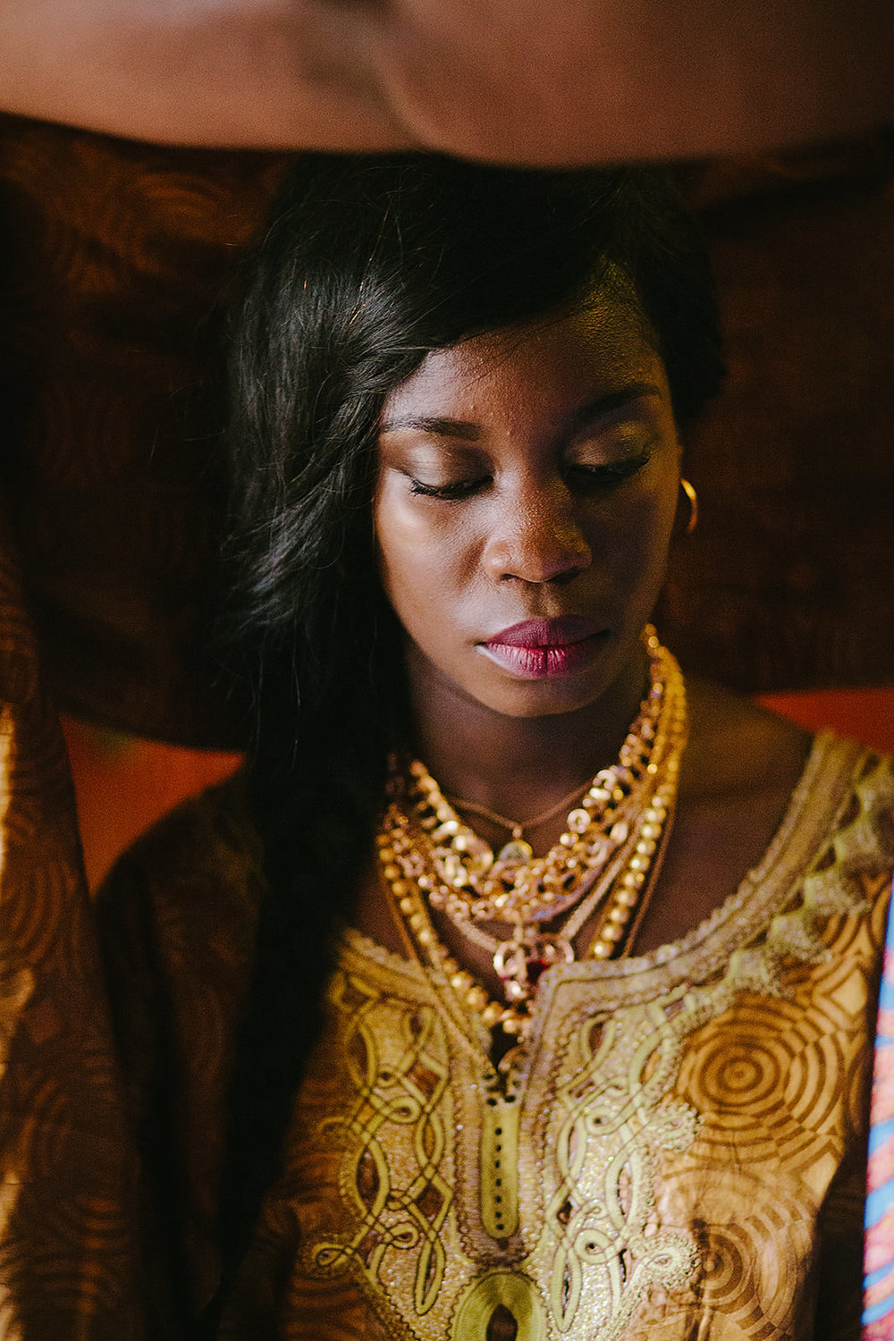 Portrait of a bride wearing golden traditional guinean wedding dress. By Oceânica Photography