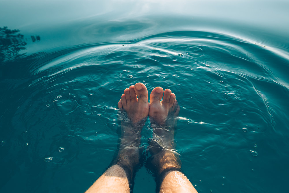 male-feet-in-outdoor-swimming-pool-P3VVQHZ.jpg