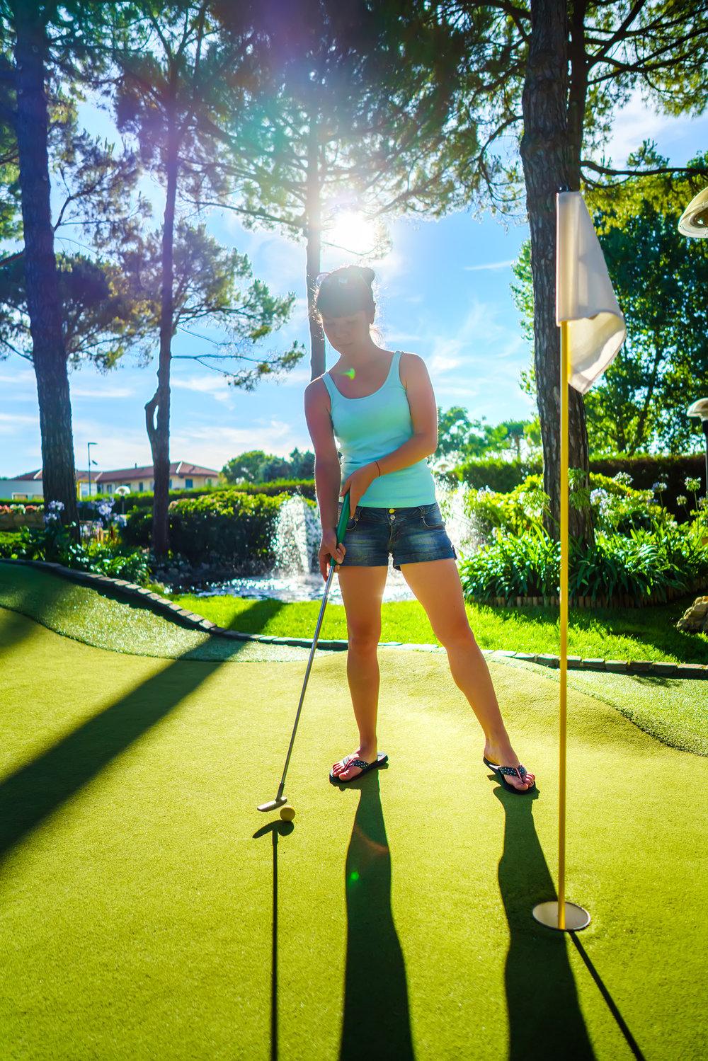 mini-golf-woman-playing-golf-on-green-grass-at-WZNL6KJ.jpg