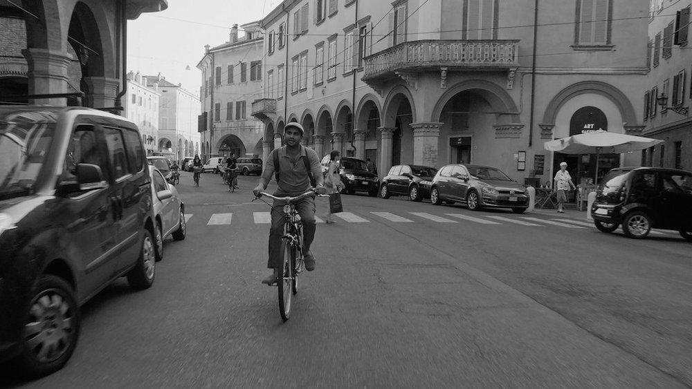 Aziz Ansari riding on bike through italy