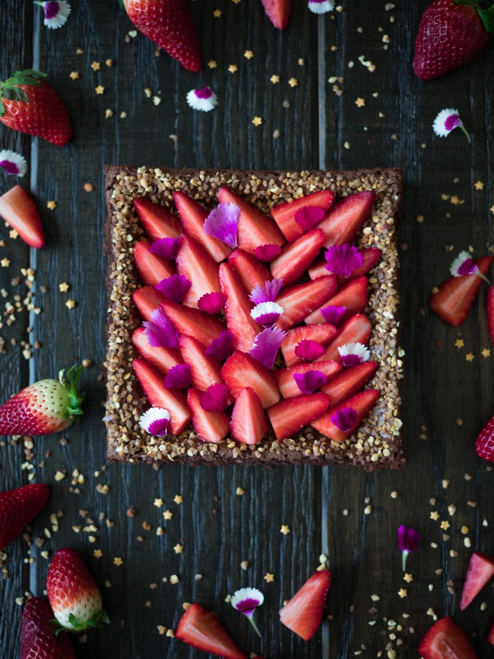 Brownie au chocolat décoré avec du praliné croustillant, des fraises et des fleurs comestibles