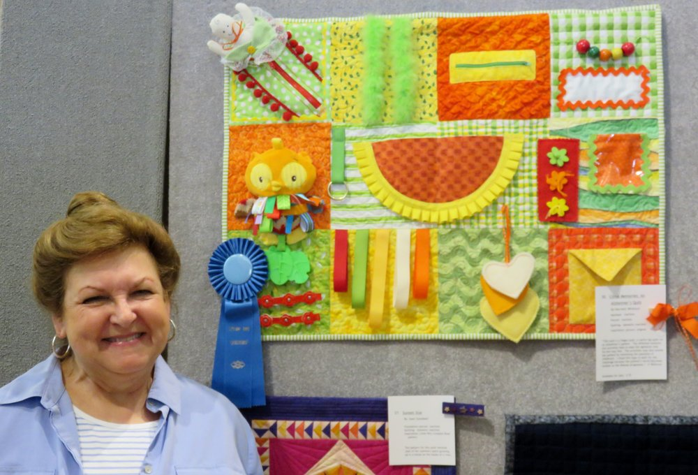 Harriett Whitlock stands with her fidget quilt.