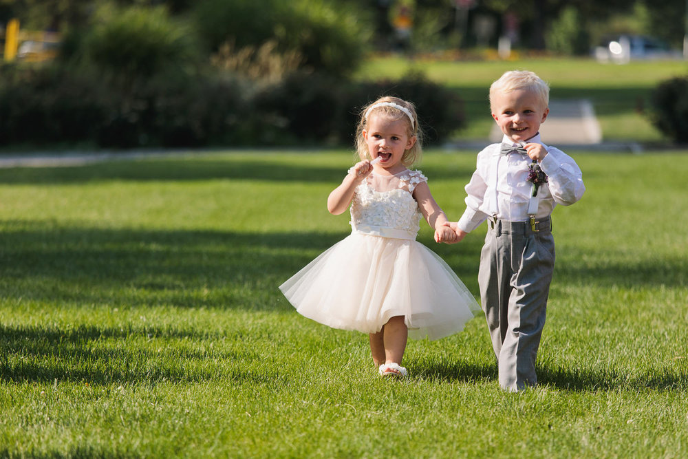a ring bearer and flower girl march during the processional during a washington park boathouse wedding in denver, colorado