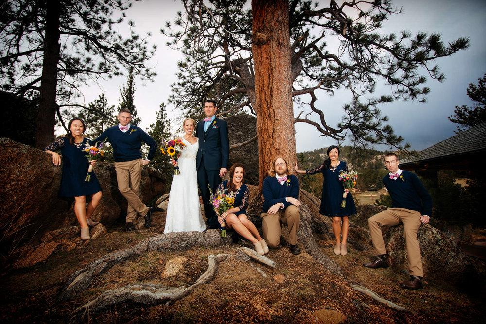 wedding party relaxes on the rocks during a black canyon inn wedding in estes park, colorado