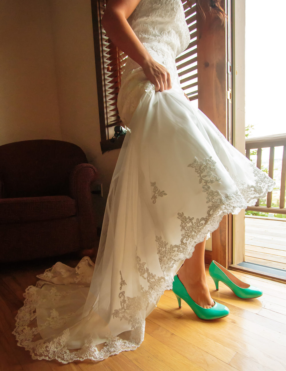 Bride slips into shoes during a Taharaa Mountain Lodge wedding in Estes Park, Colorado