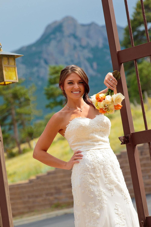 bride relaxes next to entrance gates during a Taharaa Mountain Lodge wedding in Estes Park, Colorado