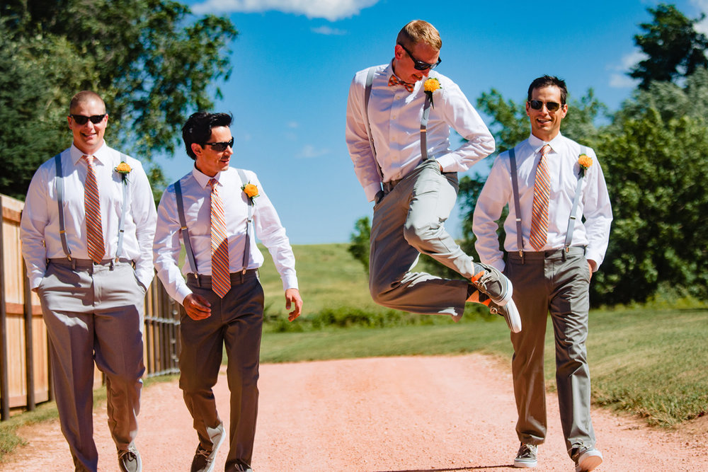 Groom jumps for joy with groomsmen during a preserve and bingham hill wedding near fort Collins, Colorado