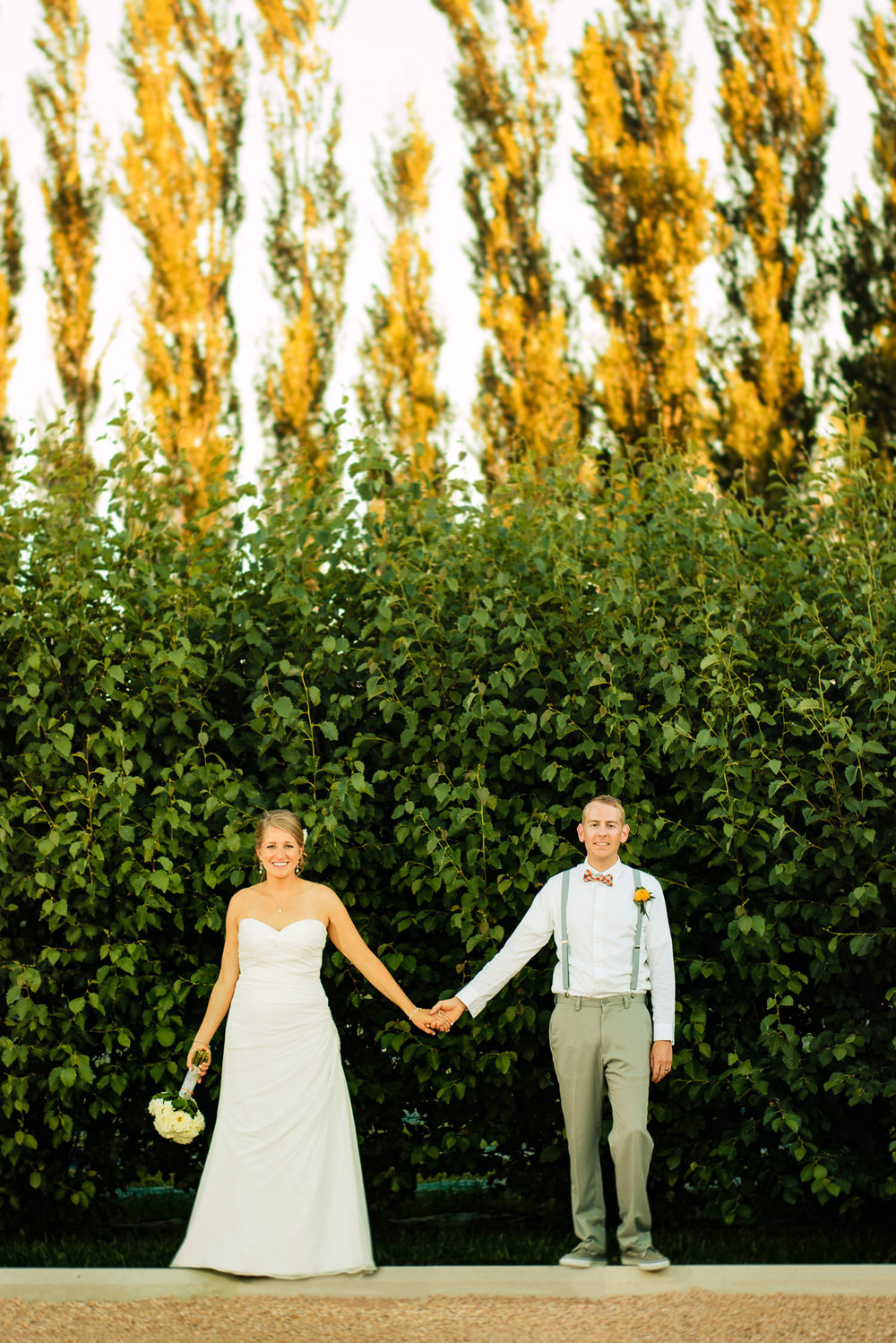 bride and groom hold hands in a summer breeze during a preserve at bingham hill wedding near Fort Collins, Colorado.
