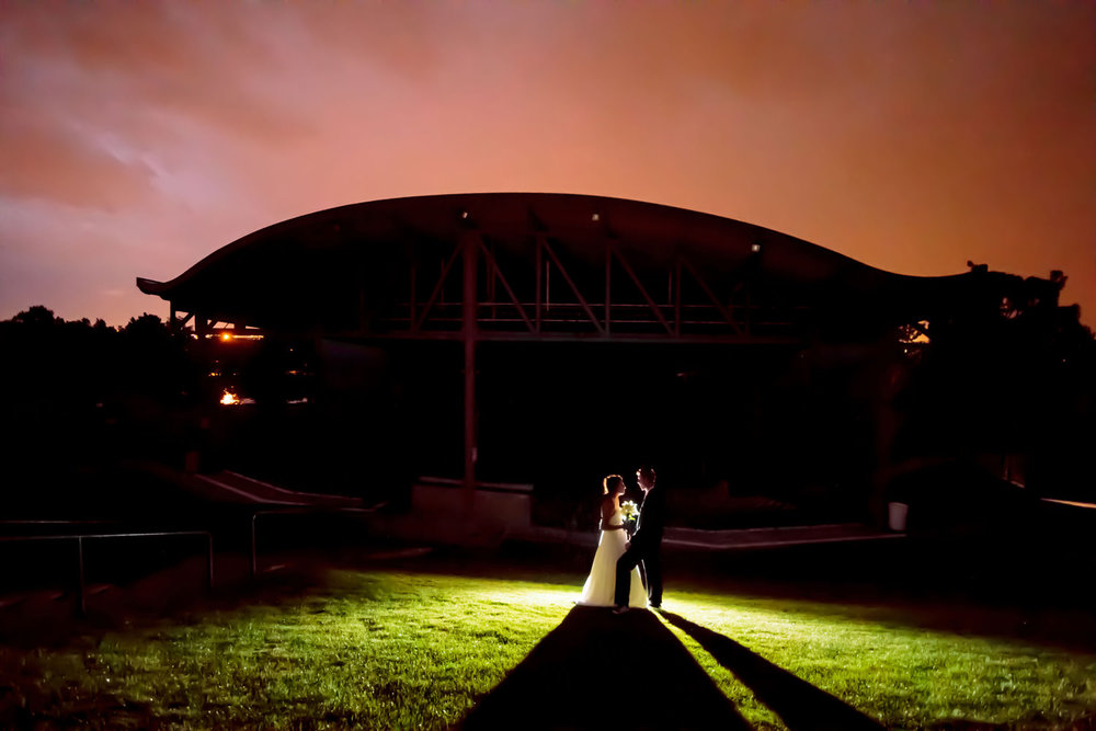 bride and groom relax under a pink sky during an arvada center wedding in arvada, colorado