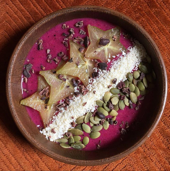 Food Bebo's frozen banana grapefruit pink dragon fruit maca powder flax seeds water, topped with star fruit coconut shreds pumpkin seeds cacao nibs coconut sugar