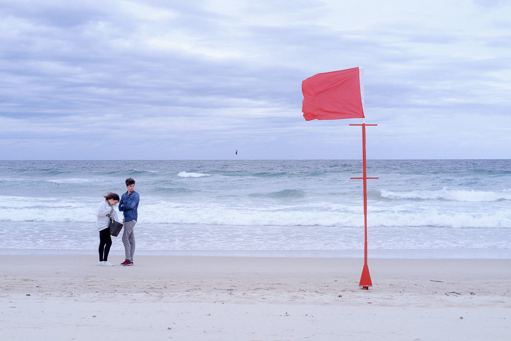 Surfers-beach-couple-and-red-flag.jpg