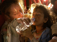 U.S. Army Sergeant Kornelia Rachwal gives ayoung Pakistani girl a drink of water. - by Technical Sergeant Mike Buytas of the USAF, public domain no rights reserved.This file was a candidate in Picture of the Year 2007, is a featured pictureon Wikimedia Commons and is considered one of its finest images.Cropped, remixed by Deborah Hartmann Preuss..