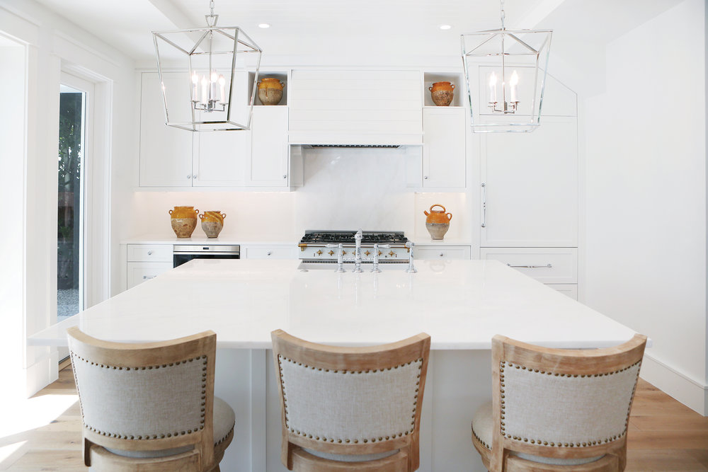 Architectural lighting hangs over a large marble island with plenty of space for prep and eating. The kitchen features a gas range and high-end appliances. Modern shaker-style cabinets are softened by more traditional pulls and handles.