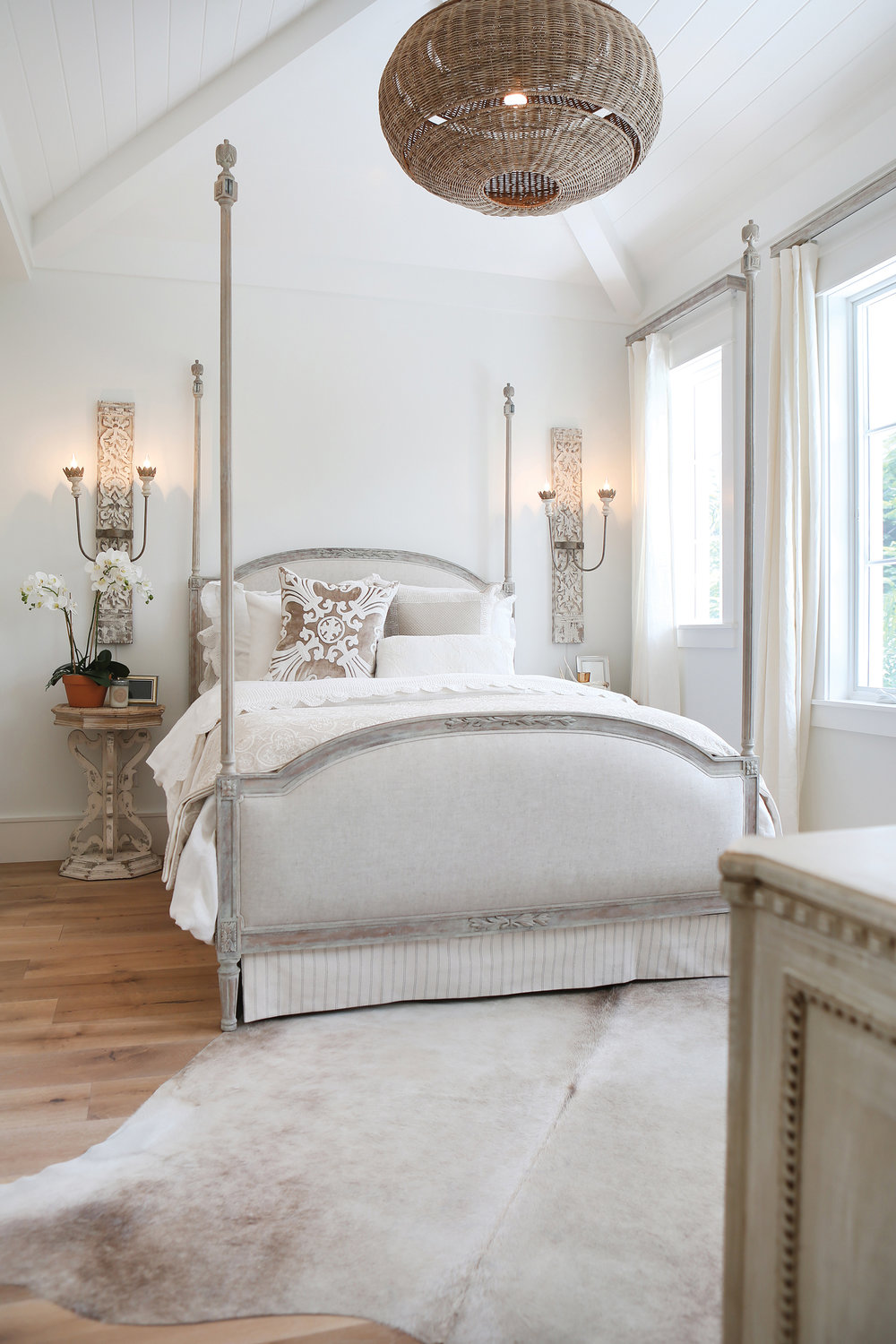 A guest bedroom provides a cozy space for family and friends. While many four-poster beds can feel heavy, Williams uses one with delicate posts in keeping with the airy feel of the room. Dramatic sconces flank the bed and draw the eye up to the ceiling details and the woven light fixture above. A hide rug anchors the room.